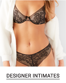 A woman in a black lacey bra and panty set with an open front white sweater. Shop designer intimates.