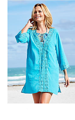 woman wearing a teal long sleeved beach cover up. Shop cover ups.