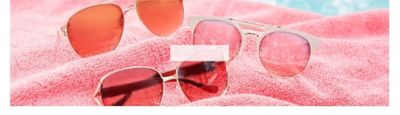 An assortment of sunglasses on a pink beach towel. Shop sunglasses.