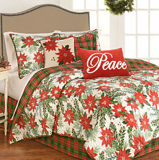 A bed made with a poinsettia patterned quilt, matching pillows, other holiday-themed pillows & white sheets. Shop quilts.