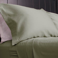 A bed made with green sheets & green & pink pillows. Shop sheets.