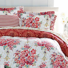 A bed made with a holiday-themed comforter & pillows. Shop bed in a bag.