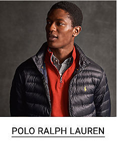 A young man in a black packable quilted down jacket, over a red quarter zip sweater. Shop Ralph Lauren.
