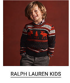 A little boy in a red, white and black christmas sweater and dark grey pants. Shop Ralph Lauren Kids.