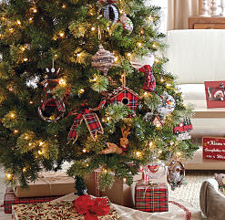 A Christmas tree with ornaments on it & presents under it. Shop Christmas trees.