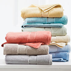 A stack of folded bath towels in a variety of pastel colors. Shop towels.