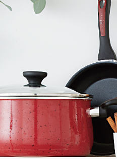 A red enamel pot with a glass lid & a black non-stick skillet. Shop cookware.