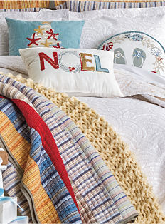 A bed made with a holiday-themed comforter & pillows. Shop bed & bath.