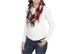 A woman wearing a multi colored scarf, a white sweater & blue jeans. Shop scarves & wraps.