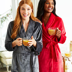 A woman wearing a gray robe standing next to a woman wearing a red robe. Shop robes.