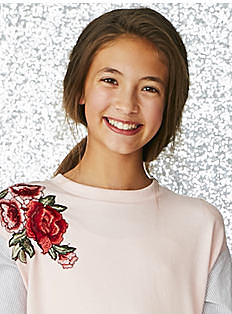 A girl wearing a white crew neck sweater with rose shoulder detail. Shop girls 7-16.