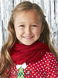 A girl wearing a red & white polka dot top with Christmas tree front graphic & a red scarf.. Shop girls 4-6X.