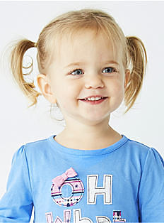 A toddler girl wearing a light blue top with pink ribbon detail. Shop toddler girls.