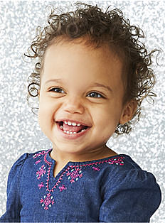 A baby girl wearing a dark blue top with purple & white neckline detail. Shop baby girls.