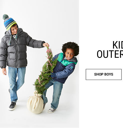 A boy wearing a gray puffer coat, multi-colored knit hat, blue jeans & gray sneakers standing next to a boy wearing a blue & green winter coat, blue jeans & gray sneakers. Kids' Outerwear. Shop boys.