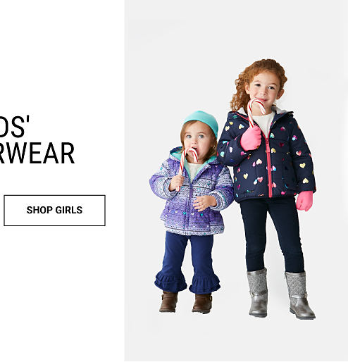 A girl wearing a teal winter hat, a purple & white winter coat, purple pants & brown boots standing next to a girl wearing a navy winter coat, navy pants & silver boots. Kids' Outerwear. Shop girls.