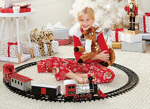 A girl sitting in the middle of a toy train set, holding a toy reindeer. Shop now.