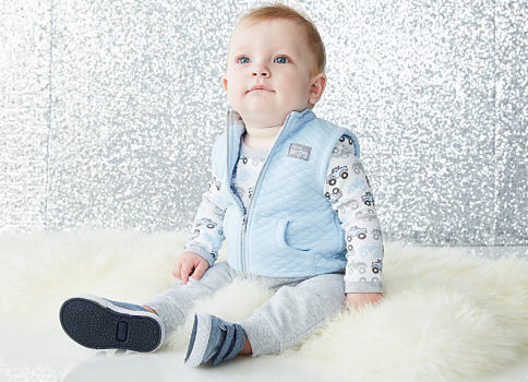 A baby boy wearing a light blue puffer vest, a long-sleeved car print shirt, light blue pants & gray sneakers. Baby's First Christmas. Shop now.