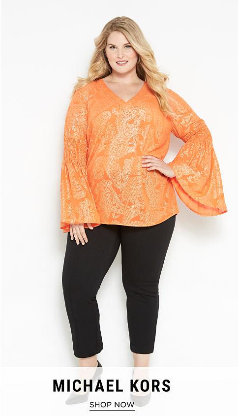 A woman in an orange & white patterned top, black pants & black shoes. Michael Kors. Shop now.