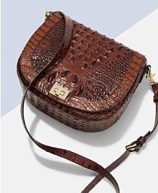 A brown hand-tooled leather handbag. Shop handbags.