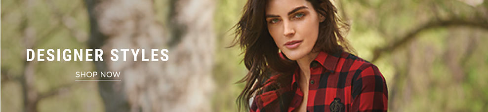 A woman wearing a red & black plaid button-front blouse. Designer styles. Shop now.