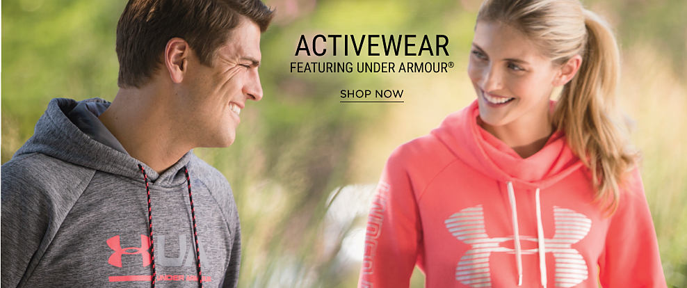 A man wearing a gray & pink Under Armour hoodie standing next to a woman wearing a coral & white Under Armour hoodie. Activewear featuring Under Armour. Shop now.