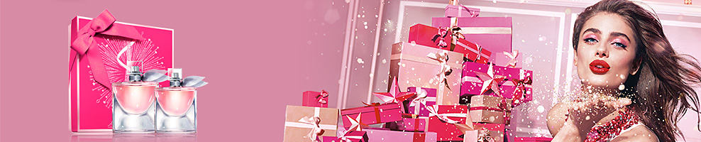 A holiday scene shows Lancome perfume, wrapped Christmas presents and a woman blowing glitter.