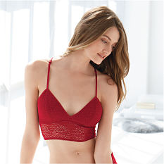 A woman wearing a red lace bralette. Shop bralettes.