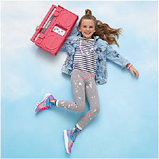 A girl wearing a jean jaclet, a black & whote horizontal striped top, gray, white & pink pants & multi-colored sneakers. Shop girls.