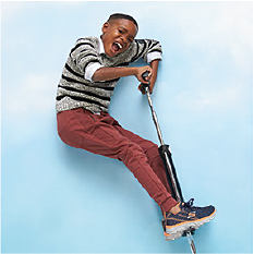 A boy wearing a gray & black horizontal striped sweater, a white button-front shirt, maroon pants & gray sneakers. Shop boys.
