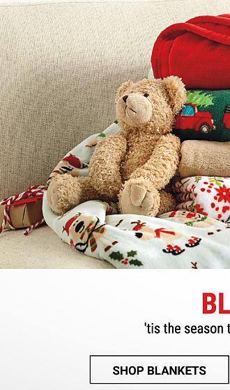 2 stacks of folded holiday-themed blankets & throws. Shop blankets.