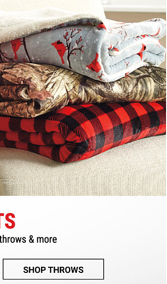 2 stacks of folded holiday-themed blankets & throws. Shop now.