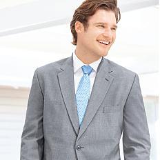 A man wearing a grey blazer, a white dress shirt & a light blue tie. Shop suits & sport coats.