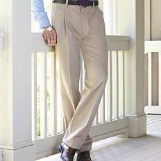 A man wearing a light blue dress shirt, beige pants & brown shoes. Shop pants.