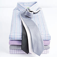 A stack of folded men's dress shirts with a couple of ties draped across the top. Shop dress shirts.