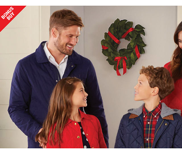 A man wearing a blue coat over a white button front shirt standing next to a girl wearing a red coat over a blue & white top, a boy wearing a blue coat over a red, green & yellow plaid flannel shirt & a woman wearing a red coat over a blue & white plaid top. Up to 60% off Crown & Ivy for the family. Exclusively at Belk.