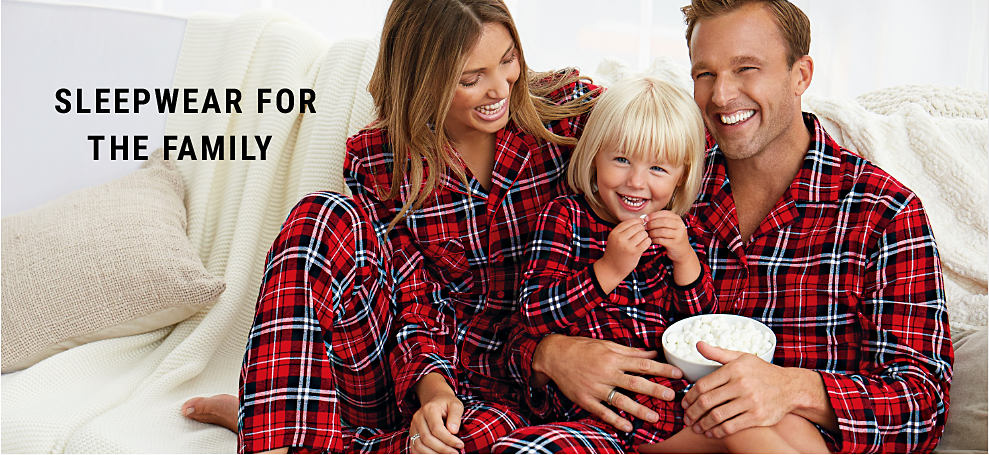 A man, woman & girl wearing matching red, black & white flannell pajamas. Sleepwear for the Family.