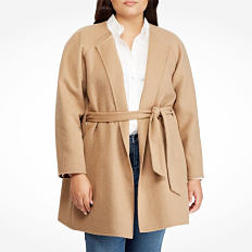 A woman wearing a beige coat over a white top & blue jeans. Shop coats.