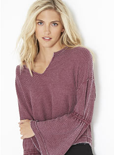 A woman wearing a burgundy distressed long-sleeved thermal top. Shop Free People.