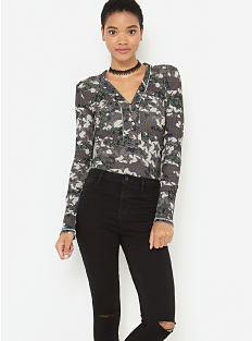 A woman wearing a gray, black & white patterned V-neck long-sleeved top, distressed black jeans & black shoes. Shop William Rast.
