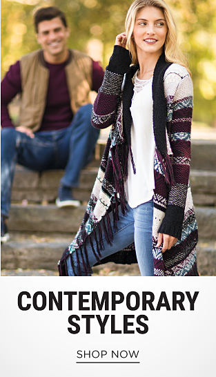 A woman wearing distressed blue jeans & a multi-colored long sweater with fringe detail. Contemporary Styles. Shop now.