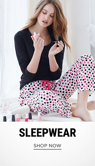 A young woman weraring a black long-sleeved sleep top & white sleep pants with black & pink polka dots & pink bow detail. Sleepwear. Shop now.