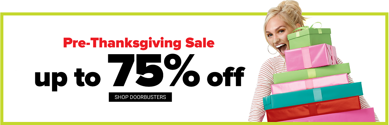 A woman wearing a white & red horizontal striped long sleeved top carrying a stack of wrapped gifts. Last Day. Pre Thanksgiving Sale Doorbusters. Up to 75% off. Shop all doorbusters.