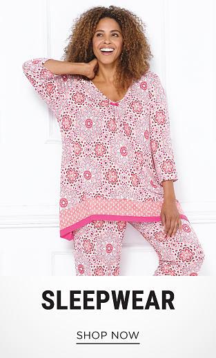 A woman wearing pink & white patterned pajamas. Shop sleepwear.