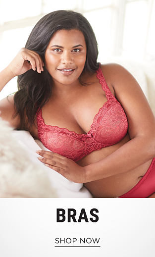 A woman wearing a red lace bra & red panties. Shop bras.