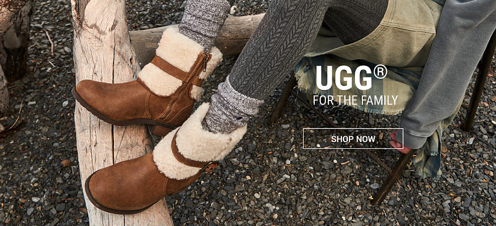 A woman wearing brown leather fleece-lined boots & gray leggings. Ugg for the family. Shop now.