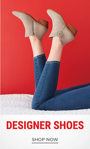 A woman wearing blue jeans & beige suede booties. Designer Shoes. Shop now.