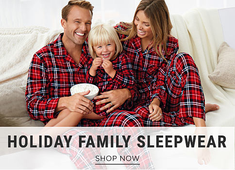A man, woman & a girl wearing matching red, black & white plaid flannel pajamas. Holiday Family Sleepwear. Shop now.