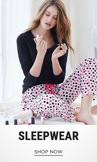 A woman wearing a black sleep top & white sleep pants with pink & black polka dots. Sleepwear. Shop now.