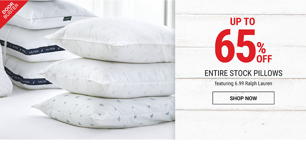 An assortment of different styles of pillows on a mattress covered with a white fitted sheet. DoorBuster. Up to 65% off entire stock pillows feraturing 6.99 Ralph Lauren. Shop now.